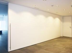 Puerta corredera de gran dimensión de 7,20x2,30m. Realizada con tableros de MDF atamborados interiormente con una cuadrícula del mismo material, consiguiendo un espesor final de hoja de 8cm. Fotografías Grupo GUBIA.