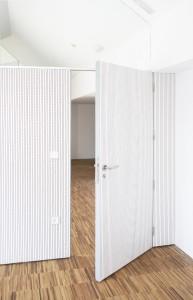 Puerta acústica de madera a medida terminada en tablero melamínico blanco fonoabsorbente. Fotografías Grupo GUBIA.